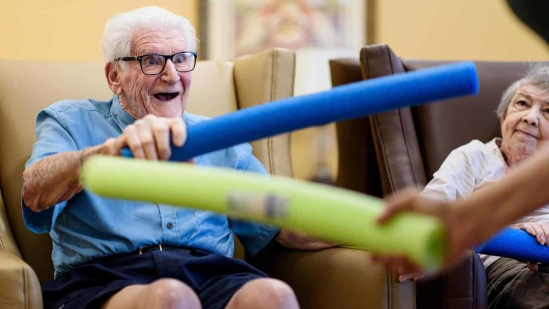 Smiling senior man participating in memory care community activity