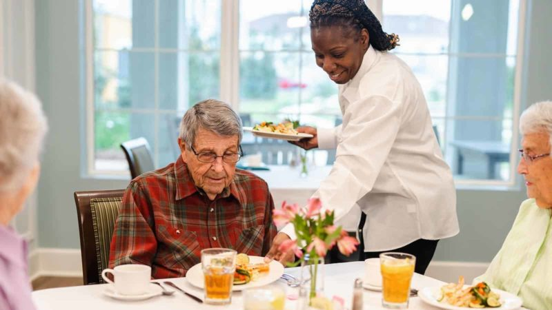 Dining staff serving meal to senior man in memory care community