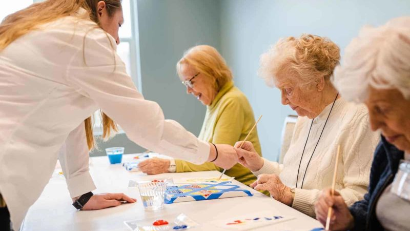 Staff helping three women paint during assisted living activity