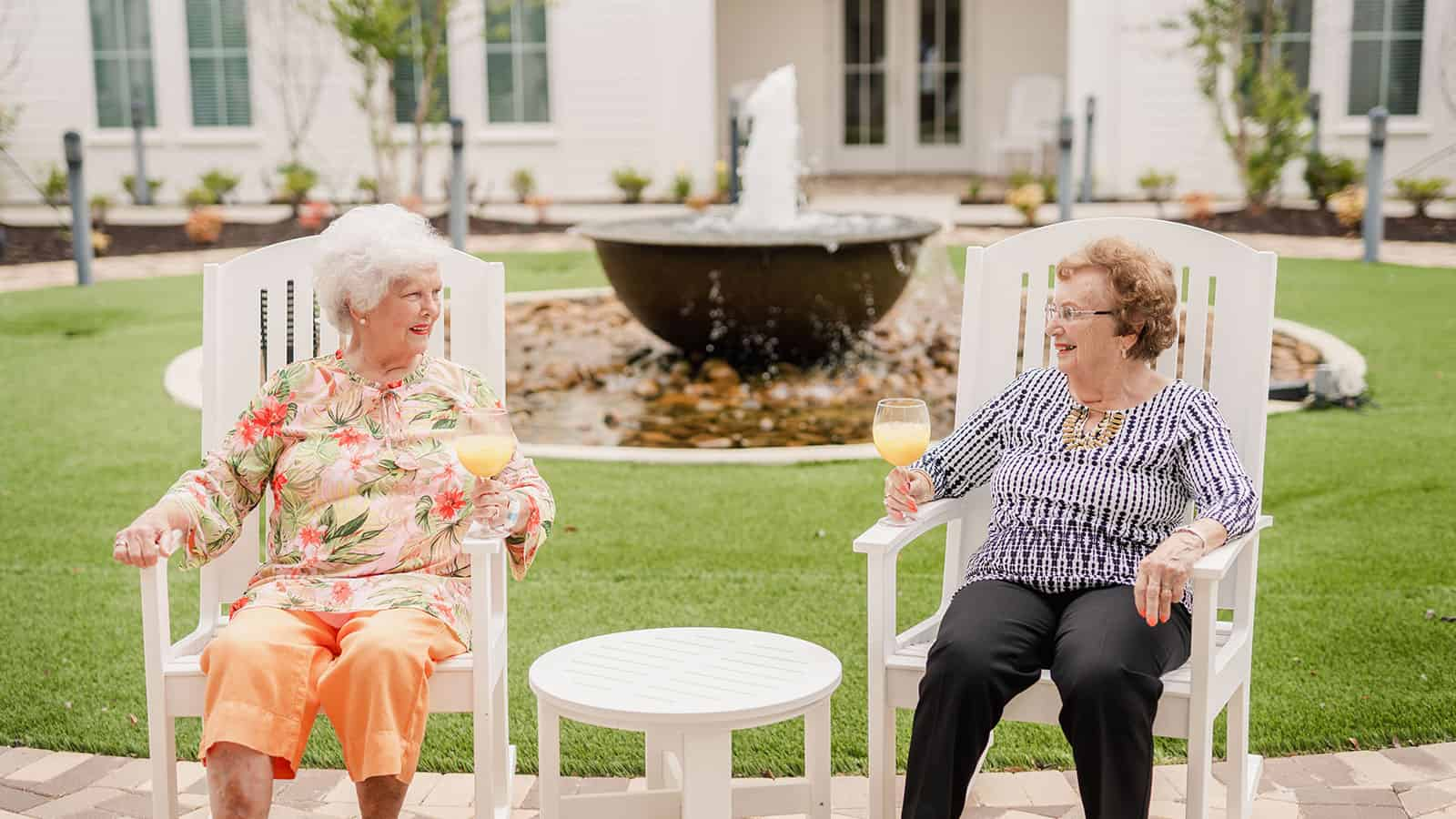 Two senior women seated in courtyard of assisted living community