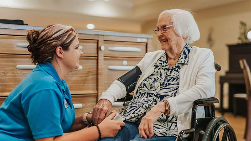 Nurse taking senior woman blood pressure in memory care community