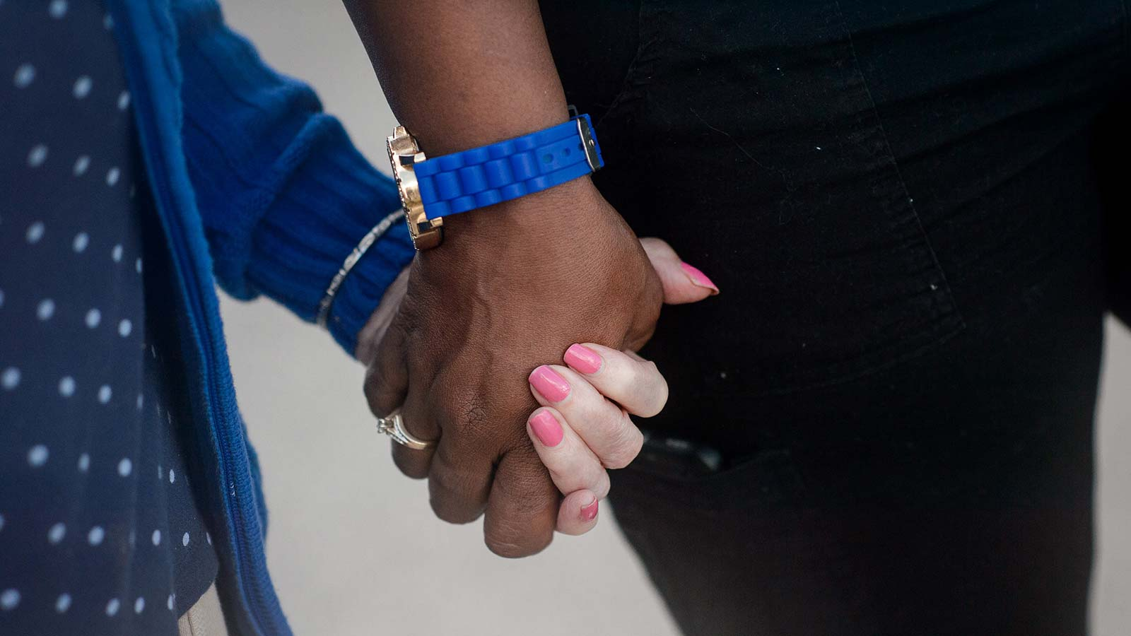 Close up of staff member and senior woman holding hands in our assisted living and memory care community